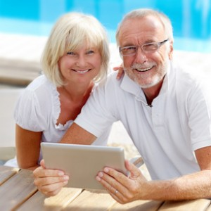 Different aged couple using a tablet pc outside